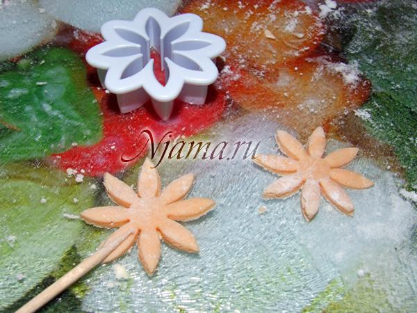 Из мастики желтого цвета делаем небольшие шарики, приклеиваем капелькой воды в центр цветочка и украшаем золотыми...